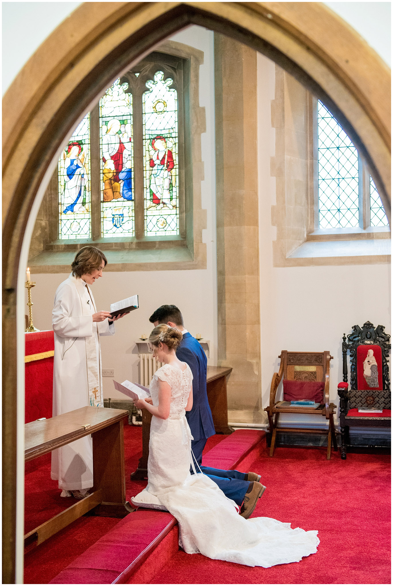 bride and groom listening to prayers from the vicar