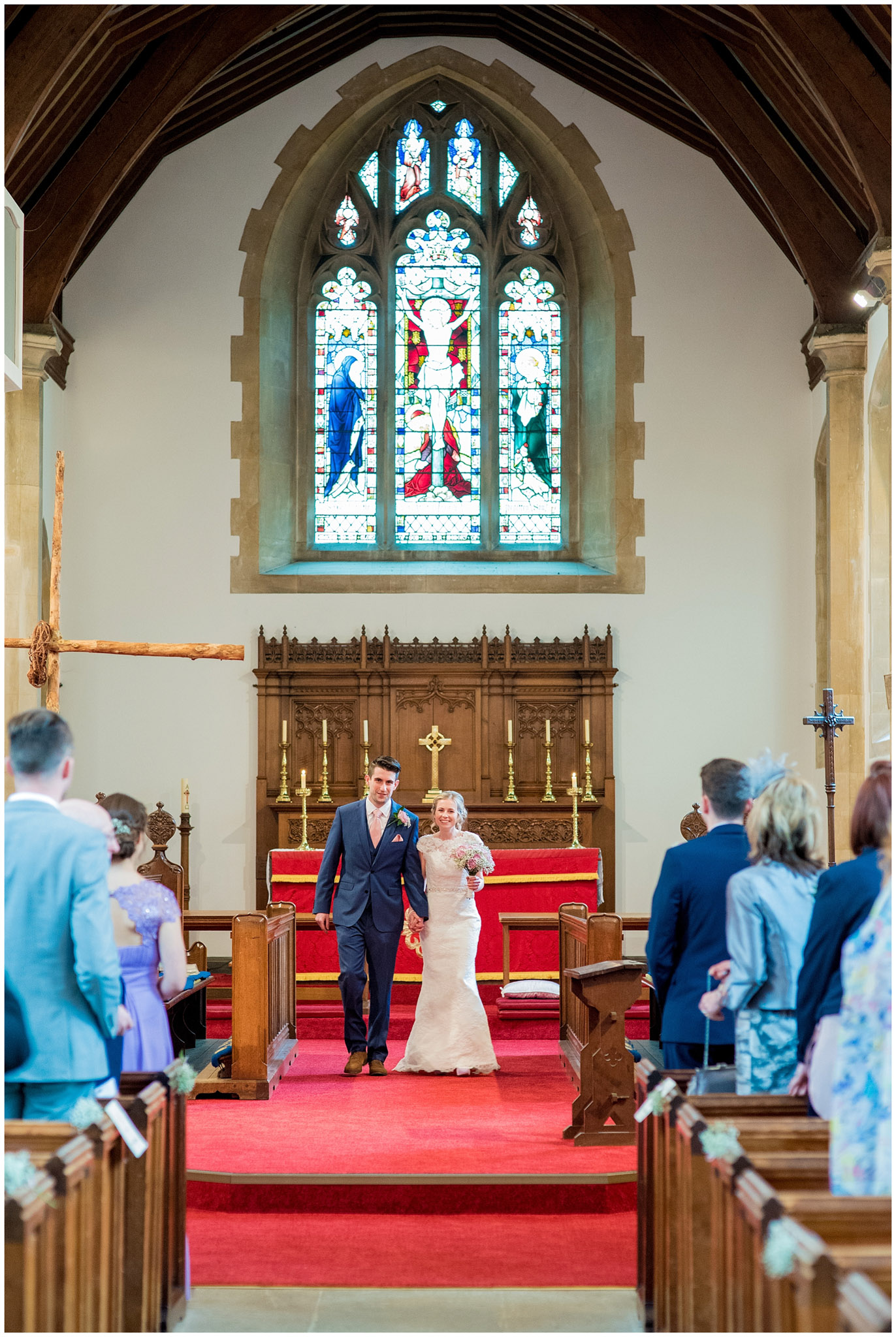 bride and groom walking down aisle smiling as husband and wife