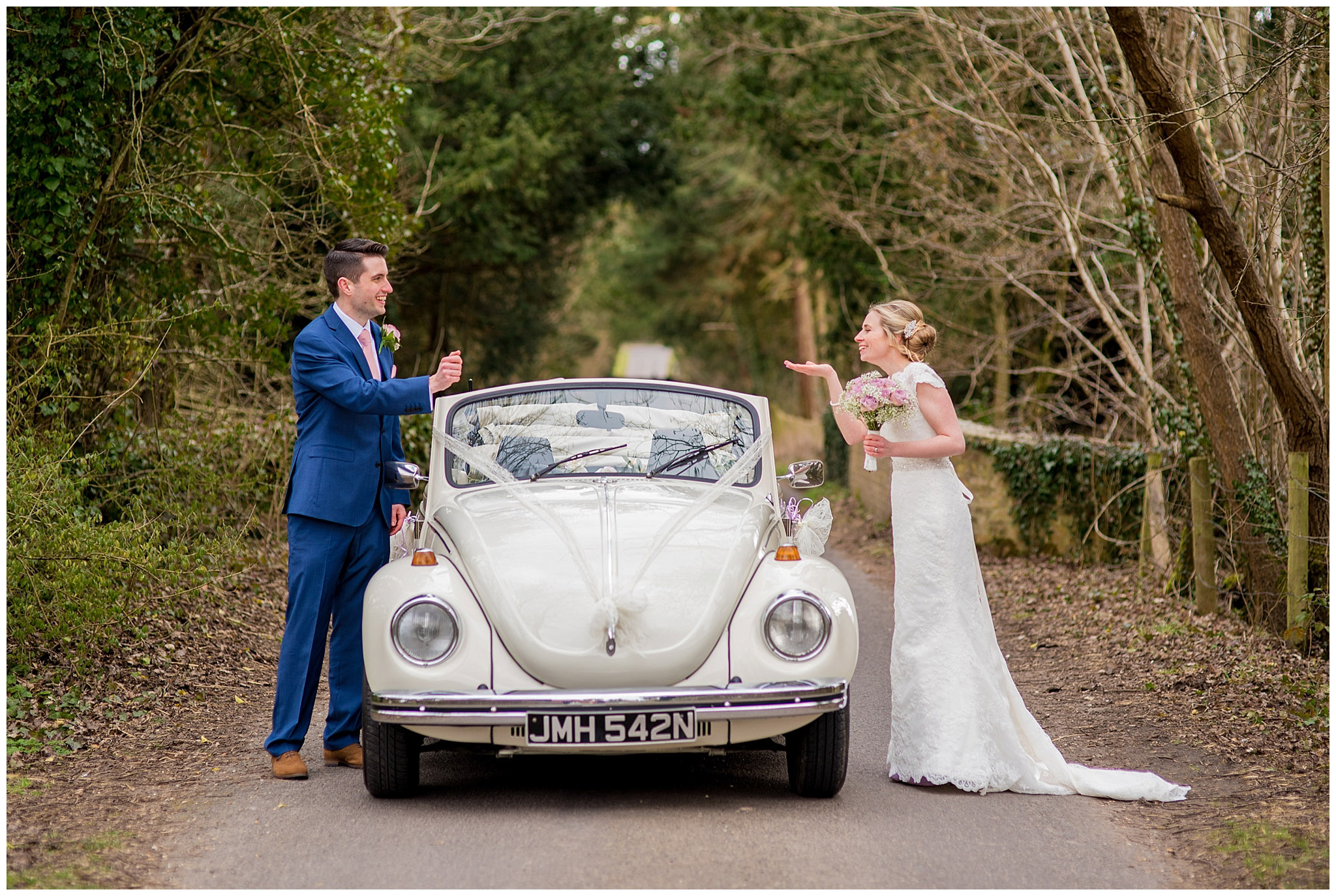 bride and groom blowing kisses over the top of their wedding car