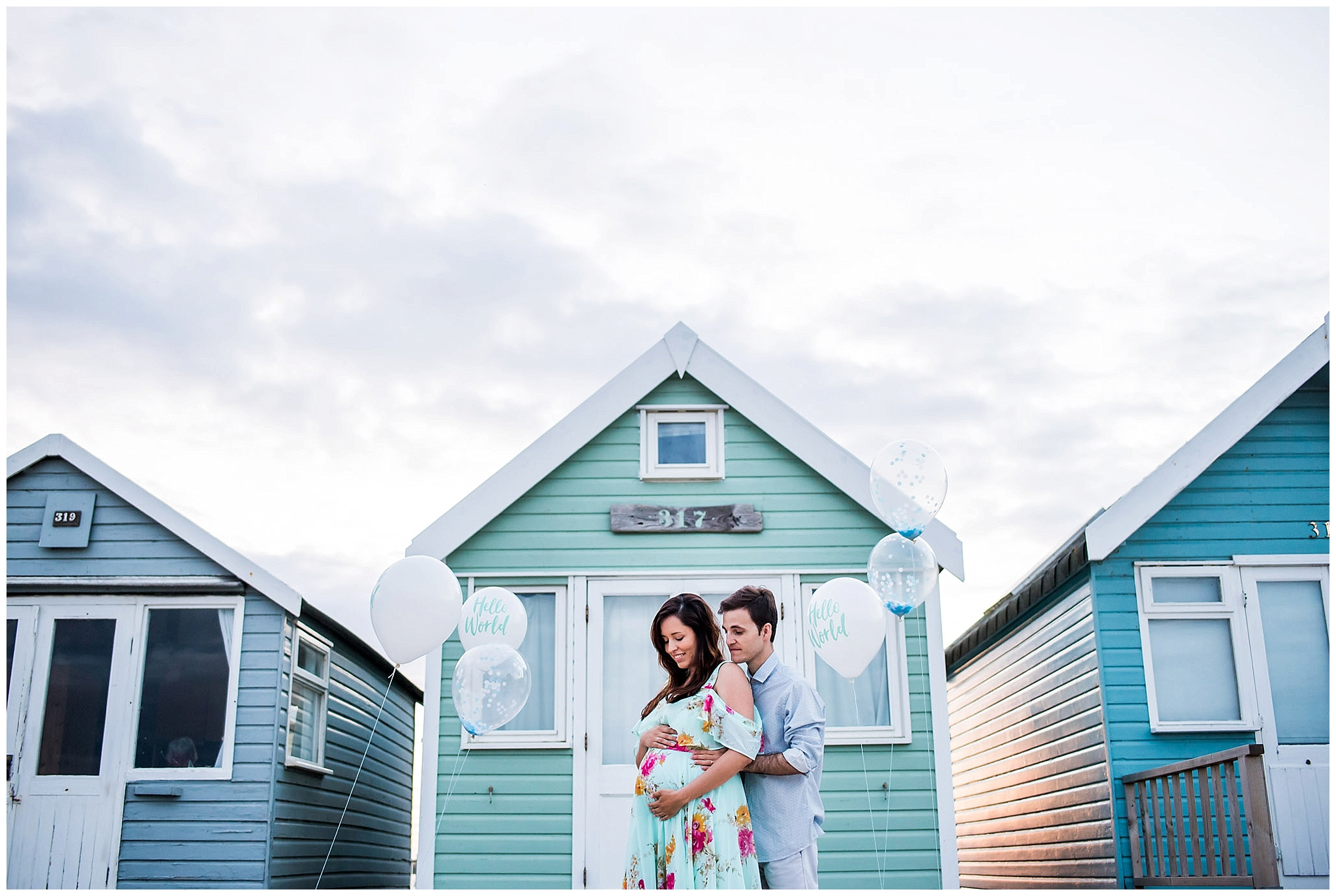 parents to be outside beach hut with baby balloons
