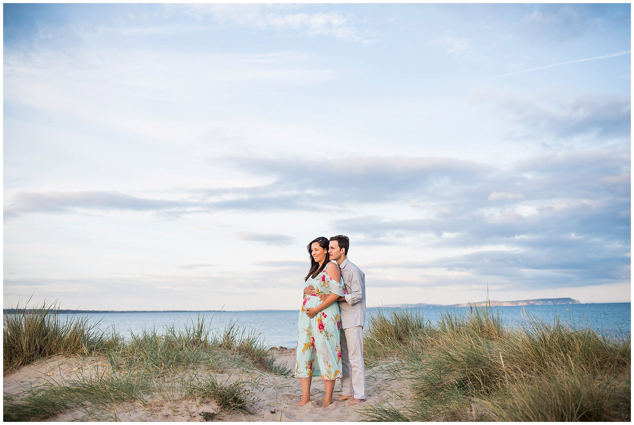 Couple stood in sand dunes seaside maternity shoot